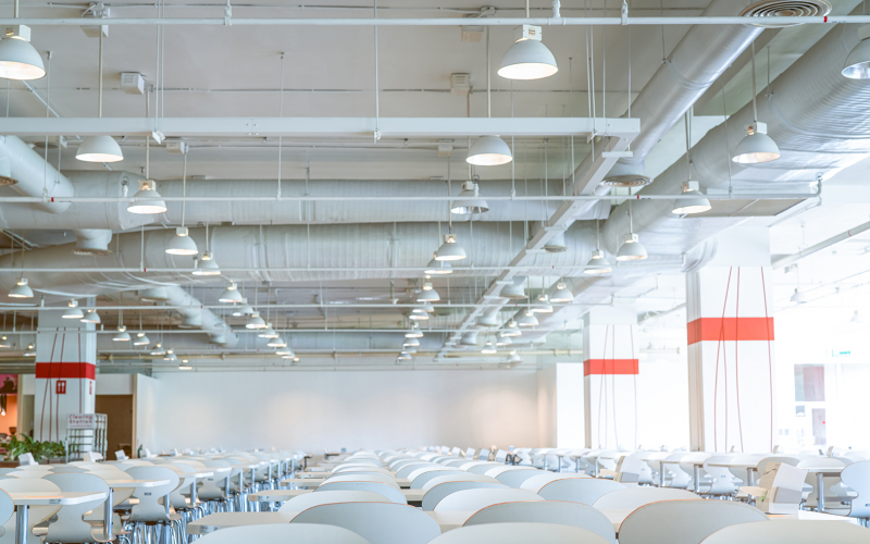 Empty white chair and table in cafeteria of shopping mall. Air duct, air conditioner pipe, , and fire sprinkler system. Ventilation system. Building interior. Ceiling lamp light. Interior architecture